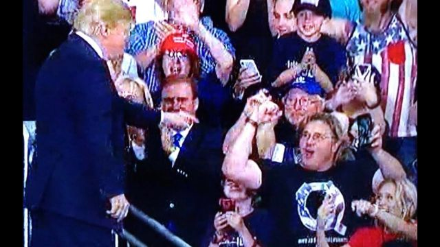 Image result for trump stands next to man with q shirt